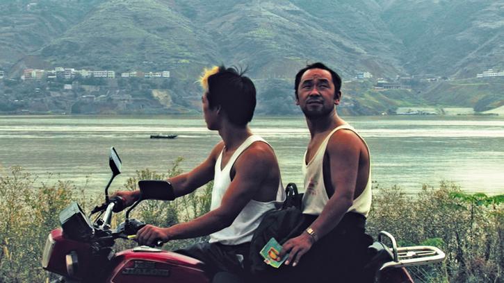 Dois asiáticos em uma moto no filme Em Busca da Vida