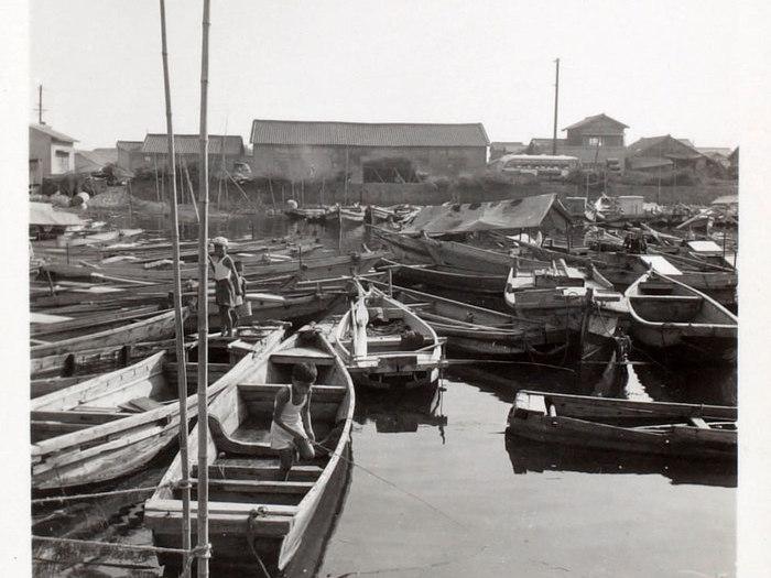 Des enfants jouant sur les barques dans un petit port
