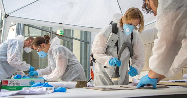 Les équipes à l'œuvre sur le chantier de nettoyage : nettoyage manuel et aspiration des moisissures.