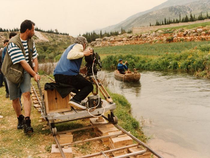 Photographie de tournage «Le Destin »(1996) © Photo Michel Y. El Esta. Youssef Chahine à la caméra, installé sur un chariot roulant sur des rails pour effectuer un travelling.