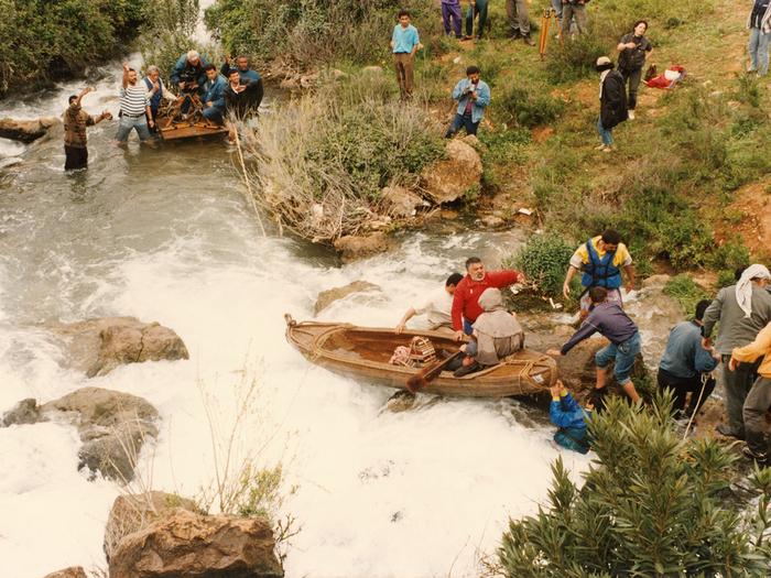 Photographie de tournage «Le Destin» (1996) © Photo Michel Y. El Esta. Youssef Chahine et son équipe technique, installés sur une barge avec la caméra, sont prêts à tourner. La barque où est assis l'acteur est encore retenue par des assistants