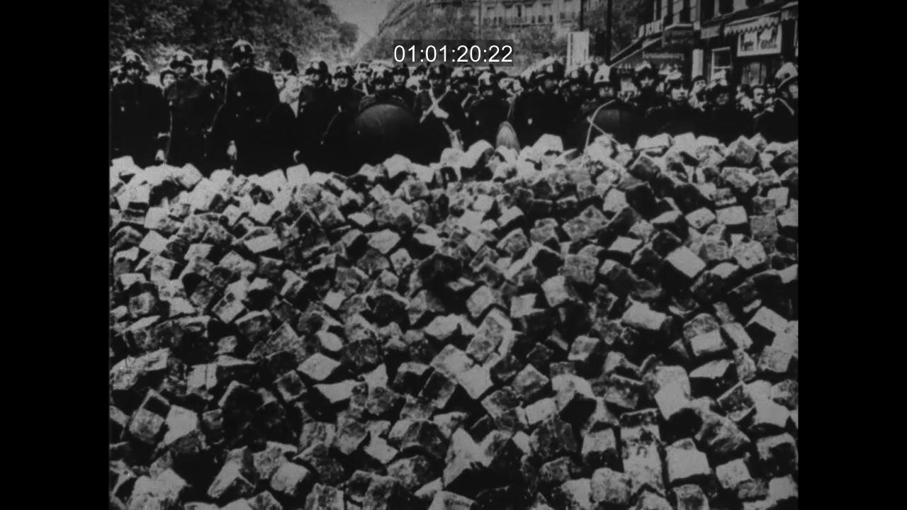 CRS massés derrière une barricade de pavés